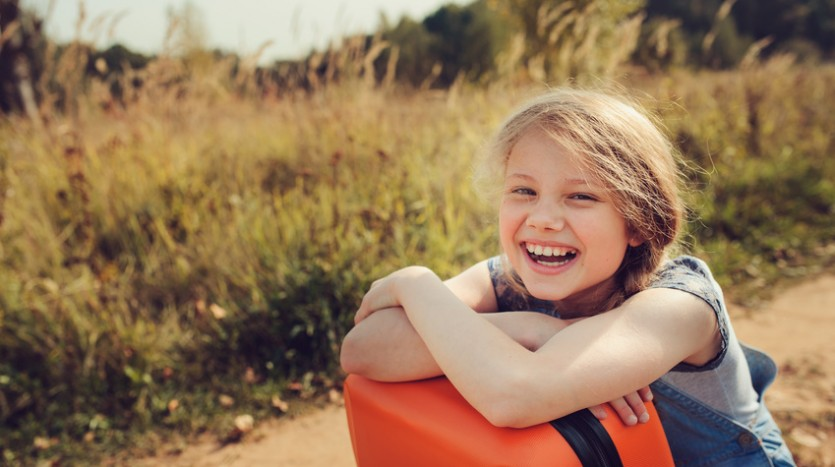 happy child girl with orange suitcase travelling on summer vacation. Kid going to countryside. Cozy rural scene